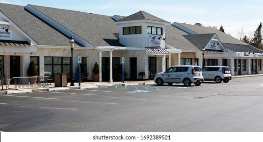 Babylon, New York, USA - 1 April 2020: A shopping centers parking lot is empty due to non essential businesses being closed due to the coronavirus pandemic.