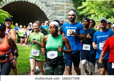 Babylon, New York, USA - 12 August 2018: Many runners racing 10K in the woods on a dirt trail after running through a tunnel with some waving at the camerman.