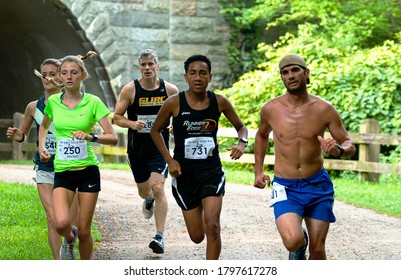 Babylon, New York, USA - 12 August 2018: Fast runners emerging from under the tunnel during the Dirty Sock 10K trail race.