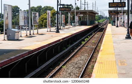 Babylon, New York, USA - 14 August 2018: Looking down the tracks on the platform at the Babylon LIRR station with signs showing the arrival and departure times.