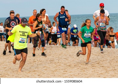 Babylon, New York, USA - 24 June 2019: Hundreds of runners are running a race on the beach as part of the New York State Parks Summer Series of races.