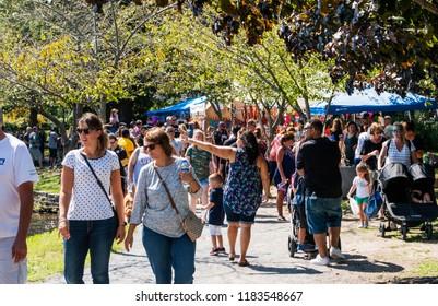 Babylon, NY, USA - 16 September 2018: People enjoying the Babylon Village fair, strolling around Argyle Lake enjoying what the vendors are offering.