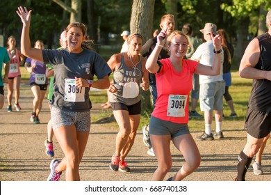 Babylon, NY, USA - 26 June 2017: Two female runners waving at camera during the Belmont Lake State Park summer series 5K race.