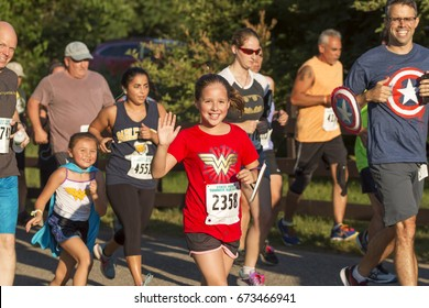 Babylon, NY, USA - 26 June 2017: Runners enjoying their race and waving to the camera while wearing super hero costumes at the Belmont Lake Summer Series 5K race.