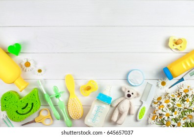 Baby's accessories near chamomile flowers over white wooden background with copy space; top view, flat lay