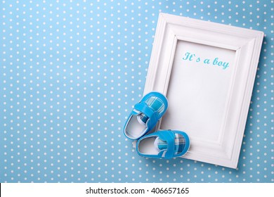 baby's bootees with a frame on a blue background