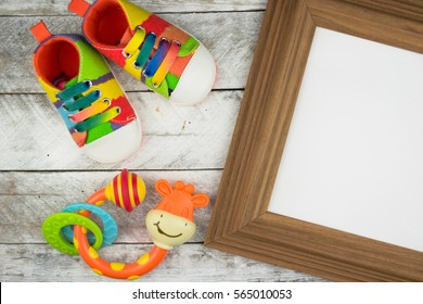 Baby's bootees on a wood with a frame