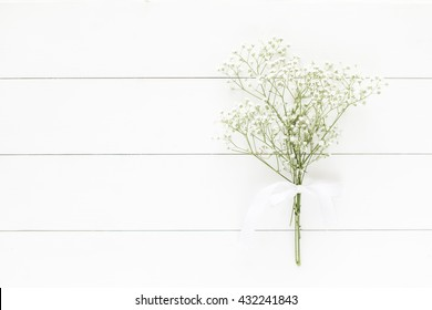 Baby's breath bouquet on white wooden background