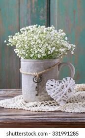 Baby's breath (gypsophilia paniculata) in grey ceramic vase on wooden background