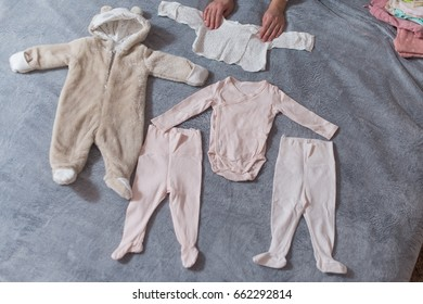 Baby's clothes laid out on bed, natural light.