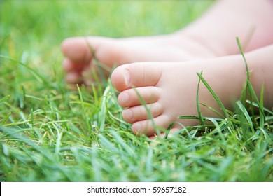 baby`s feet on green grass