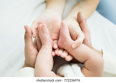 Baby's feet on parents' hands