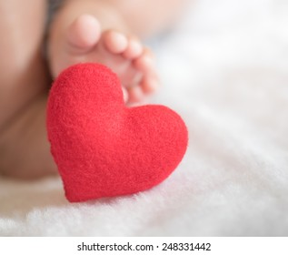 baby's feet with a red heart
