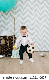 Baby's first birthday. Cute smiling baby is 1 year old. The concept of a children's party with balloons. Boy with football ball