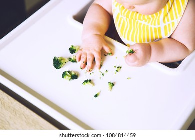 Baby's first solid food. Messy smiling baby eats and tastes with fingers vegetables broccoli in high chair. Healthy child nutrition. Mother gives to try foods to feed little child 7 months old