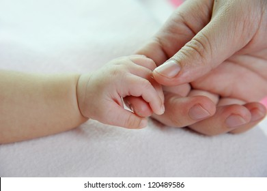 Baby's hand gripping adult finger