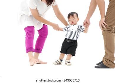 Baby's hand holding the hands of parents ,walking in studio