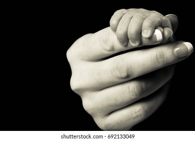 Baby's hand holding mother's finger