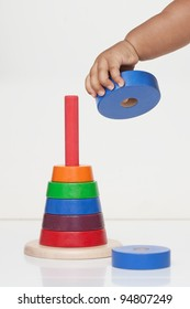 Baby's hand holding a wooden toy, demonstrating fine motor skill