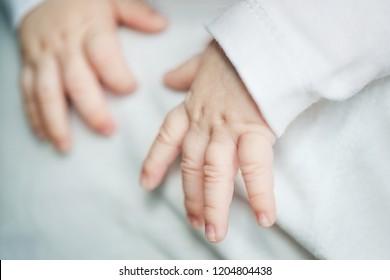 baby's hands close up. infant sleeping on dad's shoulder.