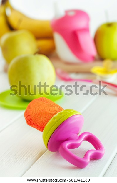 Baby's nibbler with pieces of apple for baby first feeding near fruits on the white wooden background; selective focus