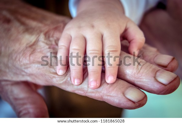 Baby's and old rough skin grandma's hand.Two generation.