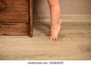 The baby's small feet are on the floor standing in tip toe in front of the dresser. High quality photo