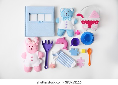 Baby's toys with photo album and socks on white background