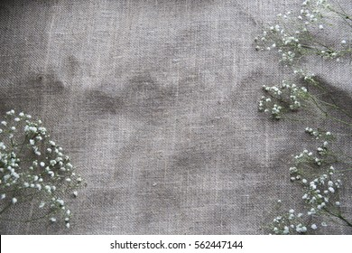 baby's-breath flowers on burlap. background layout with free text space. Flat lay composition (top view).