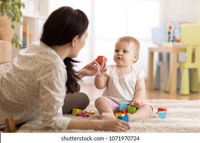 Babysitter and baby girl playing with toy cubes at home