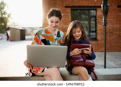 Babysitter and little school-age girl sit in the Park in their gadgets