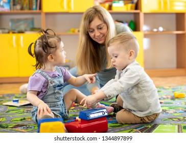 Babysitter plays with babies in nursery or kindergarten