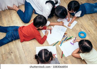 Babysitter or teacher is currently teaching children drawing with colored pencils.