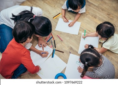 Babysitter or teacher is currently teaching children drawing with color pencils.