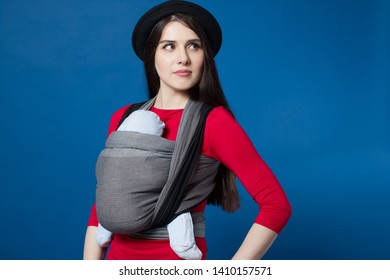Babywearing attractive young mother with baby in woven wrap carrier. Free hands and active motherhood concept idea