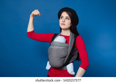 Babywearing attractive young mother with baby in woven wrap carrier demonstrating biceps . Free handed, active and inner strong motherhood concept idea