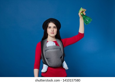 Babywearing attractive young mother with baby in woven wrap carrier with spray in her hand. Free hands and home cleaning motherhood concept idea