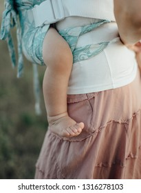Babywearing - close up of bare leg of little baby carried in buckle carrier. Mother wearing her child in sling in the fields on summer day.