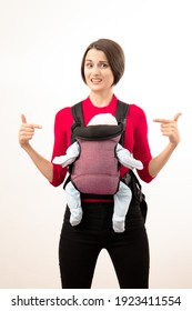 Babywearing confused young mother with baby in not ergonomic sling. Isolated on white.