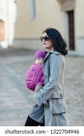 Babywearing mother carrying her child in woven wrap. Portrait of trendy woman wearing her baby son in sling and walking along city.
