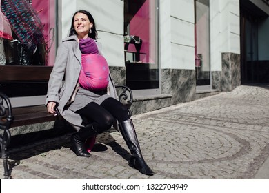 Babywearing mother carrying her child in woven wrap. Portrait of young fashionable woman wearing her sleeping child in sling sitting on bench in city.