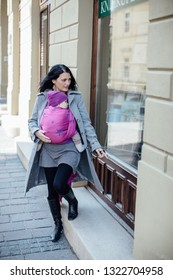 Babywearing mother carrying her child in woven wrap in the city. Portrait of trendy  woman wearing her baby in sling whilst shopping.