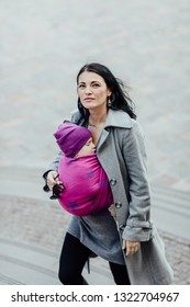 Babywearing mother carrying her child in woven wrap. Portrait of young fashionable woman hugging her sleeping child in sling.