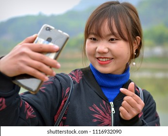 BAC HA, LAO CAI / VIETNAM - MARCH 11, 2018: Young Vietnamese H'mong hill-tribe woman takes a selfie with her cell phone, on March 11, 2018.