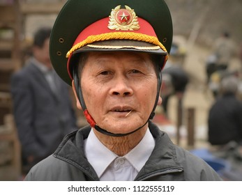 BAC HA, LAO CAI / VIETNAM - MARCH 11, 2018: Off-duty officer of the People's Army of Vietnam wears his peaked cap with insignia and poses for the camera at Bac Ha's weekly market, on March 11, 2018.