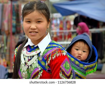 BAC HA, VIETNAM - MARCH 11, 2018: Young Vietnamese Flower H'mong hill-tribe woman with freckles carries a cute baby boy in an embroidered, traditional baby sling on her back, on March 11, 2018.