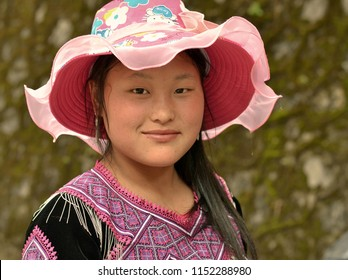 BAC HA, VIETNAM - MARCH 18, 2018: Young Vietnamese H'mong minority woman with pink sunhat wears traditional clothing and looks at the camera, on March 18, 2018.