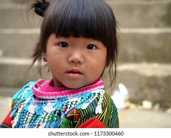 BAC HA, VIETNAM - MARCH 25, 2018: Cute Vietnamese H'mong ethnic-minority hill-tribe toddler girl with dirty face and snotty nose looks into camera, on March 25, 2018.