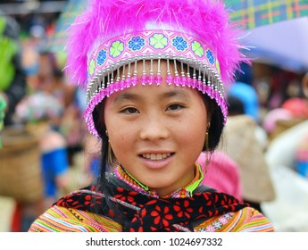 BAC HA, VIETNAM - NOV 11, 2012: Young Vietnamese Flower Hmong hill-tribe woman in colorful traditional Flower Hmong costume poses for the camera at Bac Ha's lively Sunday market, on Nov 11, 2012.