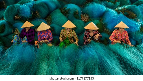 BAC LIEU CITY, VIETNAM - JULY 23, 2018: Vietnamese woman sitting repair the fishing net.